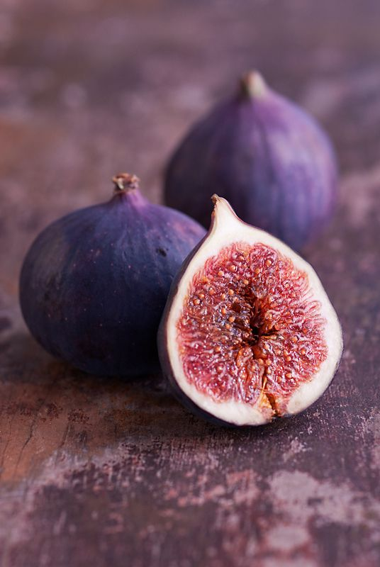 Sliced fresh Fig with whole Figs on table.